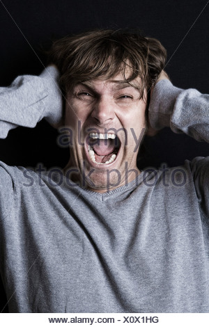 Man screaming with hands covering ears - Stock Photo