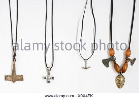 Four Viking pendants, three pendants in shape of Thor's hammer, one pendant in shape of male face with Thor's hammer - Stock Photo