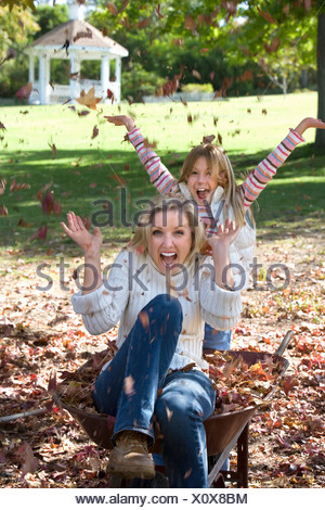 Mother and daughter 7 9 playing in garden throwing autumn leaves in air laughing portrait - Stock Photo