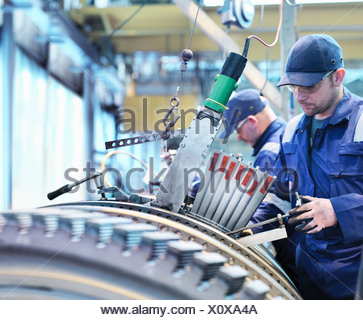 Engineers fitting blades to steam turbine in turbine repair works - Stock Photo