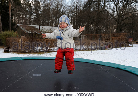 Happy little girl jumping on trampoline in winter - Stock Photo