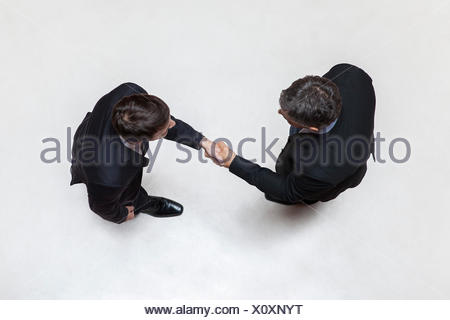 Businessmen shaking hands, overhead view - Stock Photo