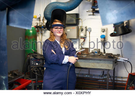 Portrait of female higher education student holding welding torch in workshop at college - Stock Photo