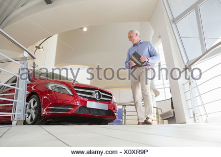 Man looking at car in car dealership showroom - Stock Photo