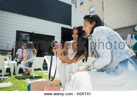 Women viewing photos digital camera on sunny photo - Stock Photo