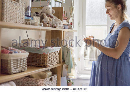 A pregnant woman in a nursery sorting out baby clothes. - Stock Photo