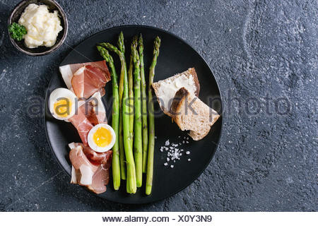 Cooked green asparagus with half boiled egg, sliced bread, butter and ham bacon served with sea salt on black ceramic plate over dark stone texture ba - Stock Photo