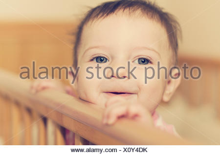 Baby girl (6-11 months) looking over her crib - Stock Photo