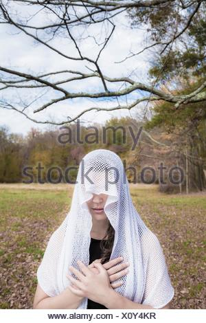 Young woman, standing in an open field, wearing a veil over her head. - Stock Photo