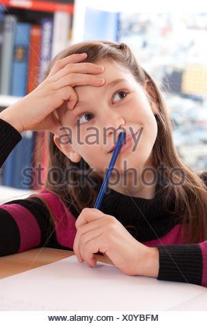 Mädchen macht Hausaufgaben und denkt nach - Stock Photo