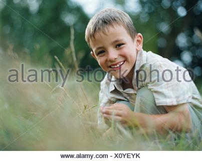 Boy crouching in grass - Stock Photo