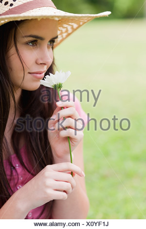Young attractive woman smelling a flower while wearing a straw hat - Stock Photo
