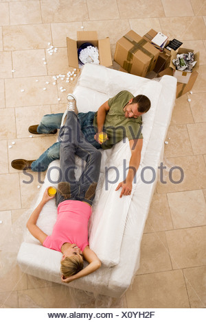 Couple moving house resting on white sofa beside boxes taking break smiling overhead view - Stock Photo