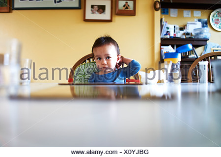 Baby boy sitting at kitchen table - Stock Photo