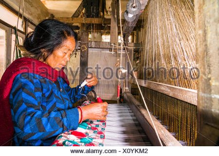 A woman is working on an old traditional loom, weaving the material for the Dhaka topi, the traditional nepali hats, Tansen - Stock Photo