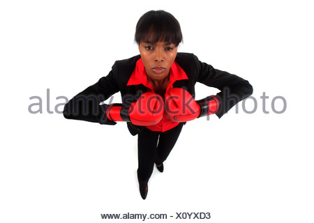 Businesswoman wearing boxing gloves - Stock Photo