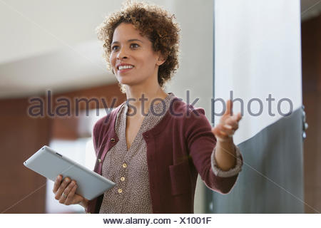 Woman at business presentation with tablet computer. - Stock Photo