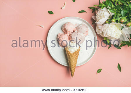 Flatlay of pastel pink strawberry and coconut ice cream scoops, sweet cones on white plate and white peonies over pastel pink background, top view, co - Stock Photo