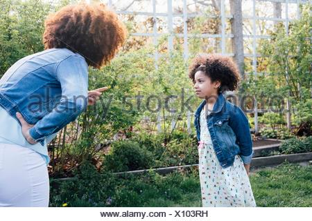 Mother scolding girl, hand on hip, pointing finger - Stock Photo