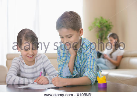 Siblings drawing together at table with mother in background - Stock Photo