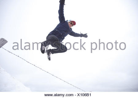 Low angle view of a young man jumping over fence - Stock Photo