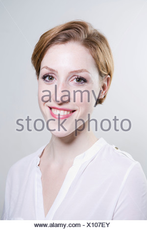 Portrait of young woman, smiling - Stock Photo