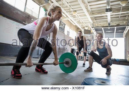 Women motivating friend weightlifting, doing barbell deadlift at gritty gym - Stock Photo