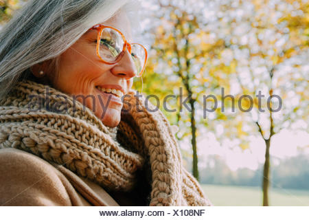 Portrait of smiling woman wearing scarf and glasses - Stock Photo