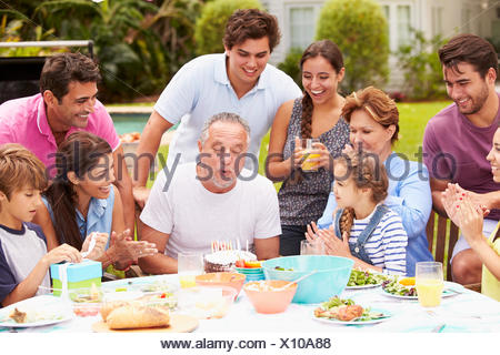 Multi Generation Family Celebrating Birthday In Garden - Stock Photo