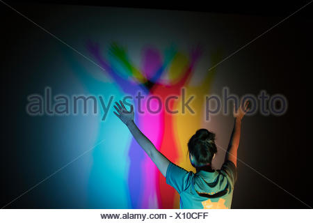 Woman casting multicolor shadows on projection screen in science center theater - Stock Photo