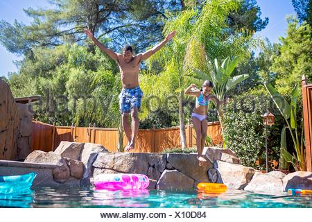 Full length front view of father and daughter mid air jumping into swimming pool - Stock Photo