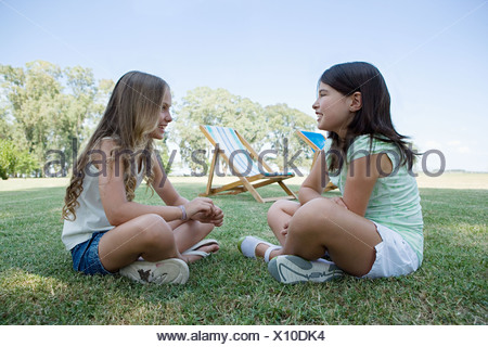 Two girls sitting on the grass - Stock Photo