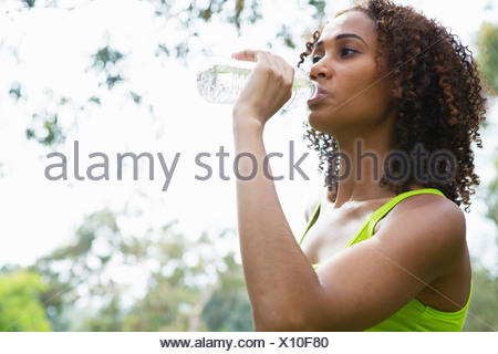 Mid adult woman drinking from water bottle - Stock Photo