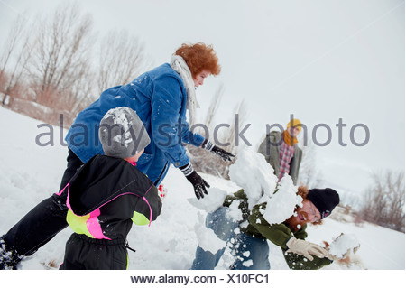 Family having snowball fight - Stock Photo