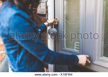 Young woman leaving house, locking front door, mid section - Stock Photo