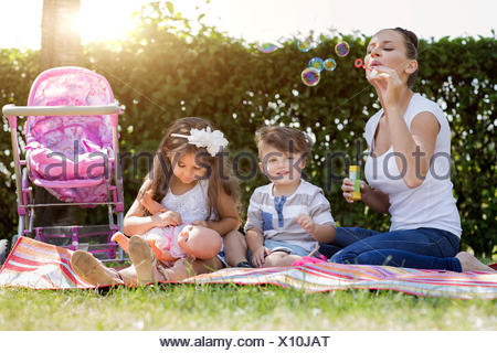 Mother and her two little children sitting together on a blanket - Stock Photo