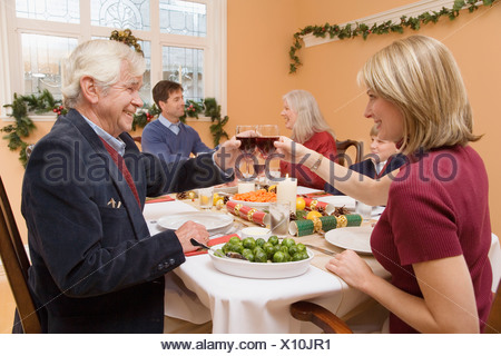 Father and daughter toasting at Christmas dinner - Stock Photo