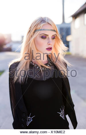 Portrait of rouged blond woman with hair-band wearing black clothes - Stock Photo