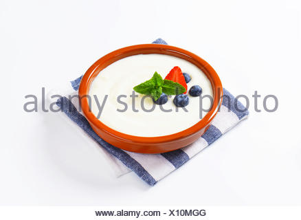 Smooth semolina porridge served in terracotta dish with fresh fruit - Stock Photo