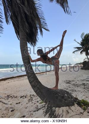 Teenage girl leaning against a palm tree doing yoga, Tulum, Quintana Roo, Mexico - Stock Photo