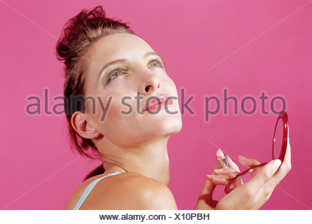 Woman putting on her makeup - Stock Photo