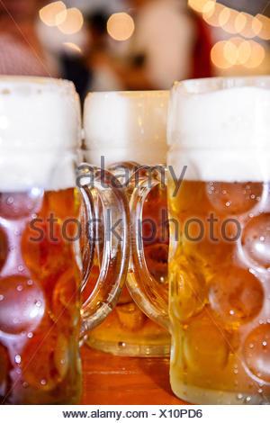 Fresh draft beer in steins at Oktoberfest Munich - Stock Photo