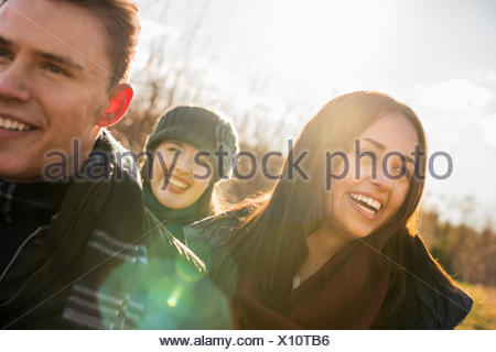 Three people, two women and a man in warm coats on a walk. - Stock Photo