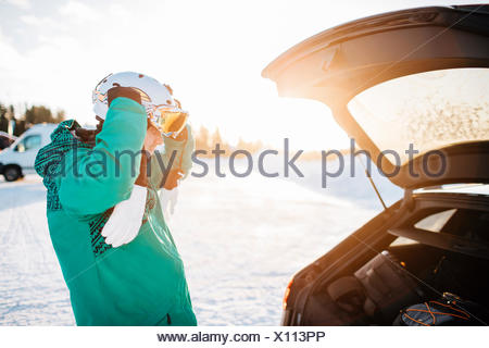 Man by a car on snow in Osterdalen, Norway - Stock Photo