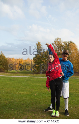 Personal trainer assisting young woman with warm up exercises - Stock Photo