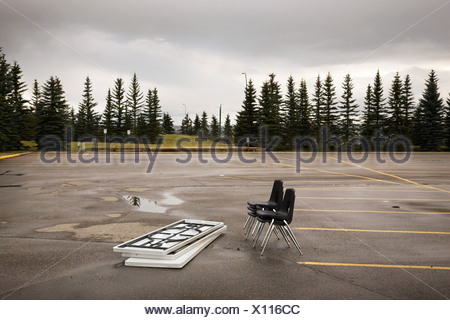 Chairs and tables left in a parking lot - Stock Photo