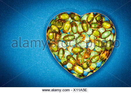 Liquid nutritional supplements in capsules in a heart-shaped container. - Stock Photo