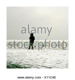 Rear view of a Man standing on pier fishing in the winter - Stock Photo