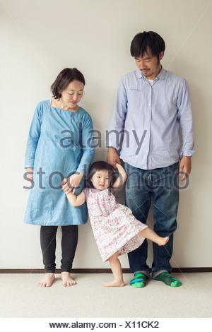 Parents holding daughter's hands, portrait - Stock Photo