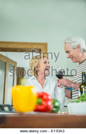 Mature couple holding glass of wine, smiling - Stock Photo